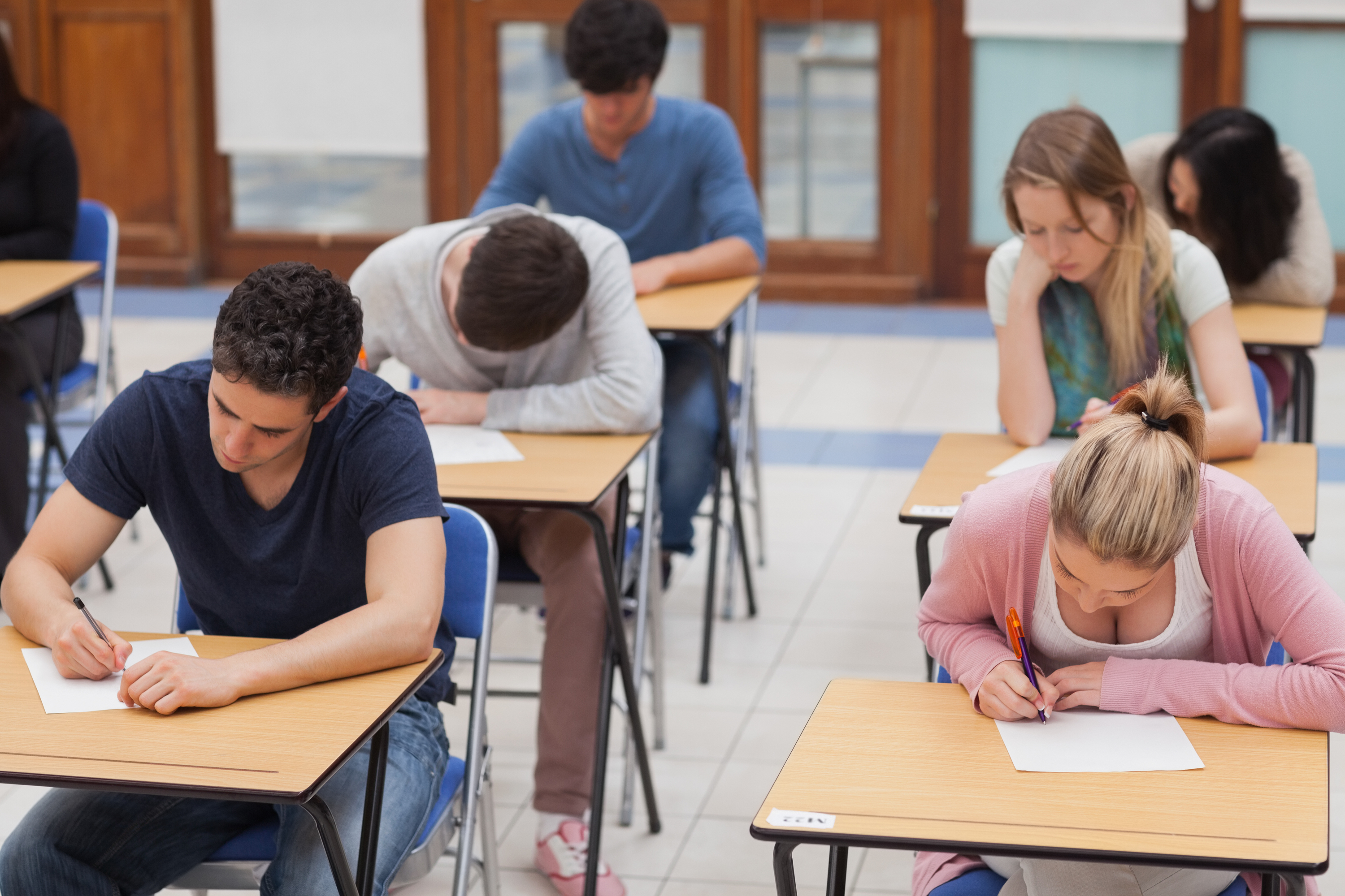 Students Sitting A Test In An Exam Hall In College